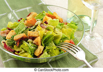 Caesar salad served in a glass bowl and white wine