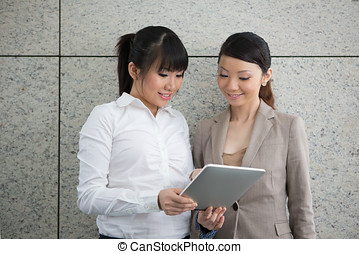 Two girls looking at a touch screen tablet.