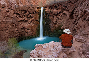 Mooney Falls - Young man sitting on a cliff watching Mooney...