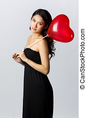 Woman holding a heart shaped balloon for Valentines Day -...