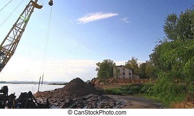 Floating crane digging sand on river side