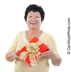 A gift - Happy mixed race Senior Asian woman holding a gift...