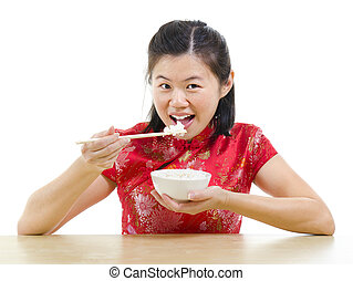 Asian woman eating rice with chopsticks over white...