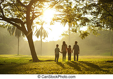 Walking towards the light - Asian family holding hands and...