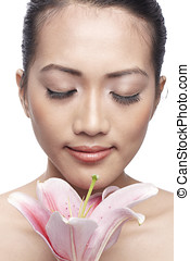 Close-up of a young Asian woman holding a lily - Close-up of...