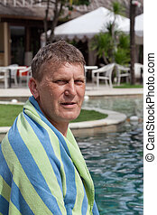 mature man in a towel sits at the pool