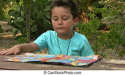 Little boy reading magazine