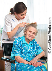 Home care - Nurse dressing the hair of a senior woman