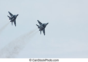 Two flying tactical russian jet fighter MiG-29 in the cloudy...