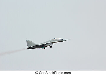 Flying russian military jet fighter MiG-29 in the cloudy sky