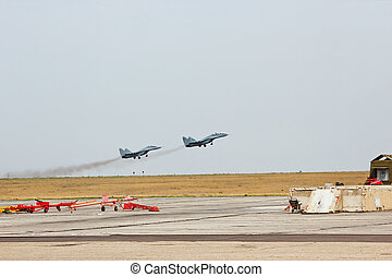 Two russian tactical jet fighter fly up from the airfield
