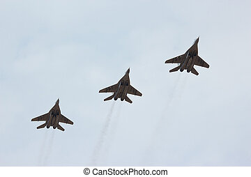 Three flying russian jet fighter MiG-29 in the cloudy sky