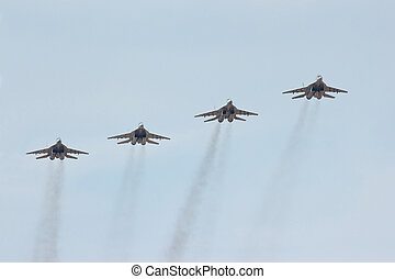 Four flying russian jet fighter MiG-29 in the cloudy sky