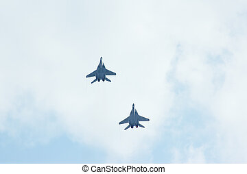 Two flying tactical jet fighter MiG-29 make maneuvers in the...