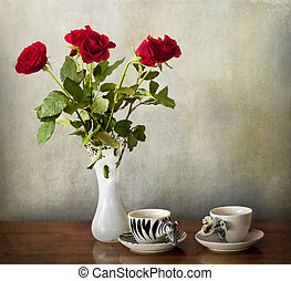 Espresso for two and a vase with red roses on a wooden table