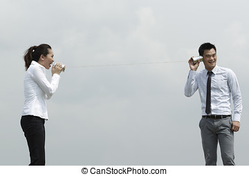 Asian Business man and woman using Tin Can Phone - This...