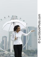 Asian business woman standing under an Umbrella