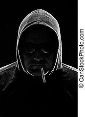 Low key portrait of a man with cigarette. studio shot.