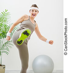 Happy fitness woman kicking in camera