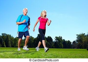 Happy jogging couple. - Happy senior couple jogging in the...