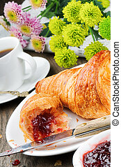 Breakfast with coffee, croissant and jam on wooden table