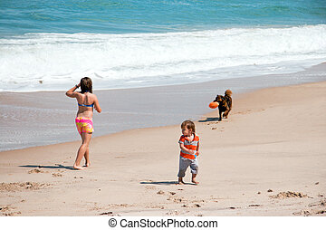 Playing on Beach - Brother sister and dog playing on sandy...