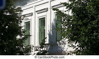 Fragment of white building and foliage