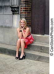 Contagious Grin - Beautiful young woman sits on steps of old...