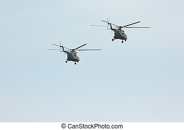 Two russian military transport helicopter MI-8 in the cloudy...