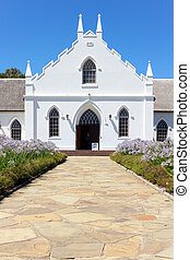 White Church in Franschhoek in front of blue sky with stone...