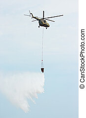 Military helicopter MI-8 extinguishes the fire with water in...