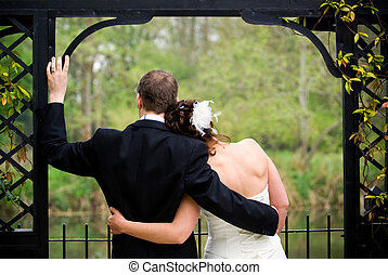 Just Married - Newly wedded couple affectionately holding...