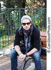 Young stylish man sitting on a bench - Young stylish man...