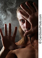 Portrait in a smoke - Portrait of the man closed by hands on...