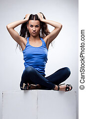 Sexy brunette sit in jeans and blue tank top
