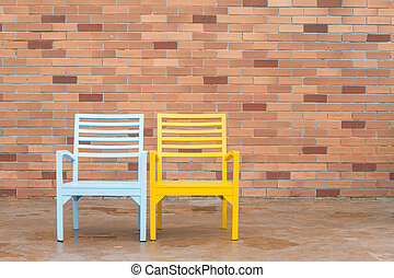 blue and yellow wooden chair and red brick wall