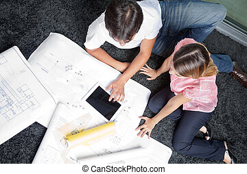 Couple Sitting On Rug With House Plans - High angle view of...