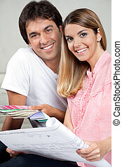Couple Making House Plans - Portrait of happy young couple...