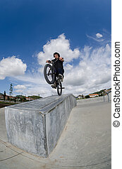 Bmx rider on a ramp over cloudy sky background.