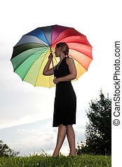 Woman with rainbow umbrella on a hill