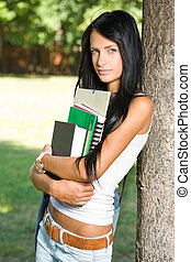Attractive slender young student girl in the park. -...