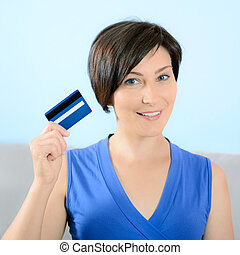 Smiling woman showing credit card - Pretty young woman with...