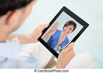 Video chat communication - A young couple talking to each...