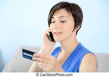 Young woman on mobile with credit card - Young woman calling...