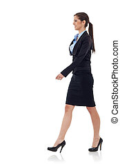 young business woman walking. She is smiling and looking...