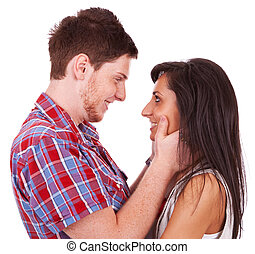 A beautiful young couple smiling at eachother while he holds...