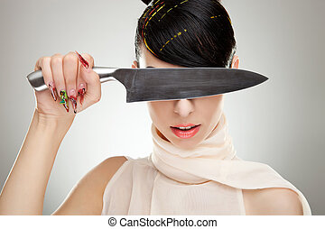 beautiful young woman covers her eyes with a knife