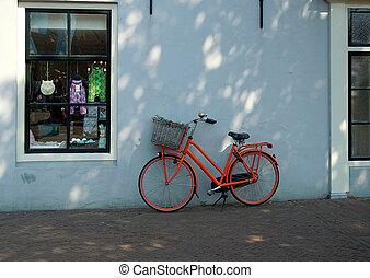 Oranje fiets tegen muur - Fiets tegen muur geplaatst...
