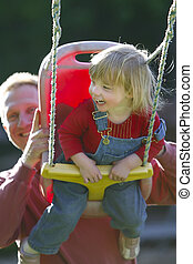 Girl on a Swing - Young blond girl on a backyard swing,...