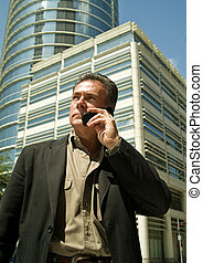 Calling His Broker - A man talking on a cell phone with...